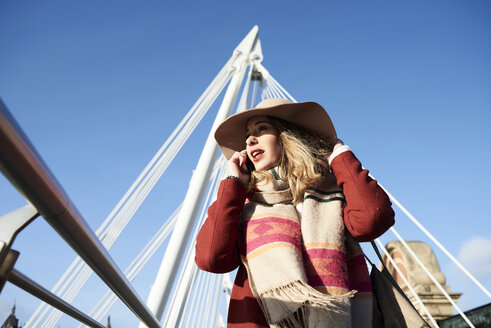 UK, London, stylish young woman talking on cell phone on Millennium Bridge - IGGF01140