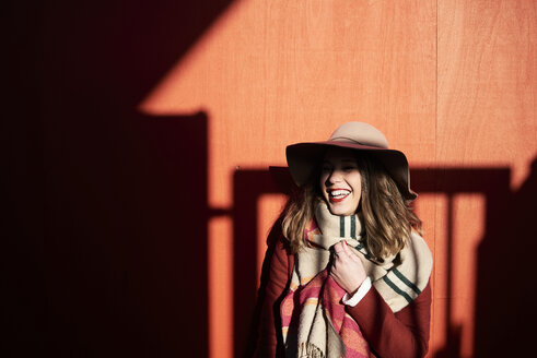 Laughing woman wearing a floppy hat in light and shadow - IGGF01149