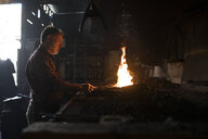 Blacksmith working at forge in his workshop - ABZF02294