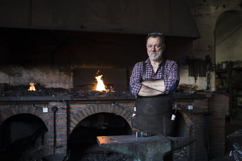 Portrait of confident blacksmith in his workshop - ABZF02303