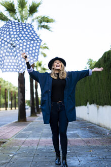 Blond woman with umbrella on a rainy day - ERRF01059