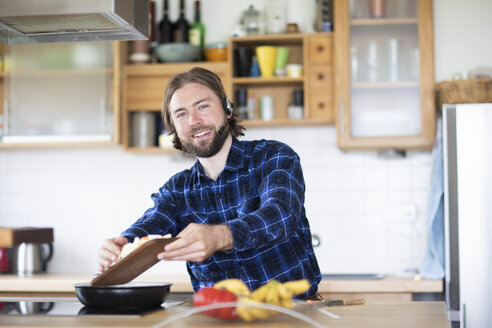 Young man with beard and plaid shirt, and headset cooking vegetables in kitchen - SGF02365