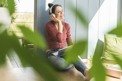 Happy woman with headphones and laptop sitting at the window at home - UUF17203