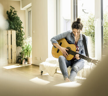 Woman sitting at the window at home playing guitar - UUF17206