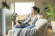 Woman with a mug sitting on the couch at home using tablet - UUF17218
