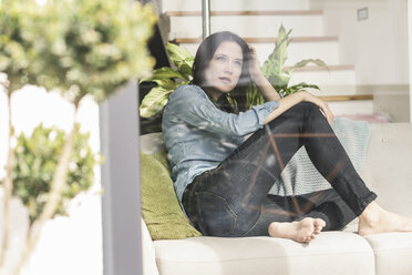 Pensive woman sitting on couch behind windowpane at home - UUF17227