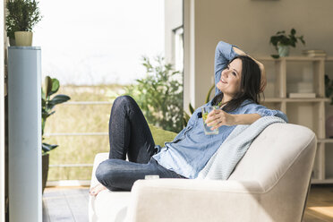 Happy woman with a glass of infused water sitting on the couch at home - UUF17230