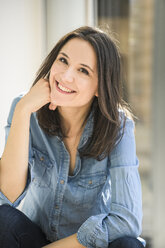 Portrait of happy woman wearing denim shirt at home - UUF17233