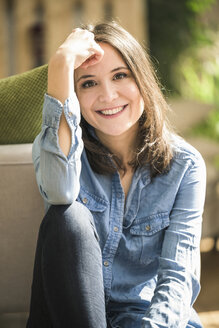 Portrait of happy woman wearing denim shirt at home - UUF17236