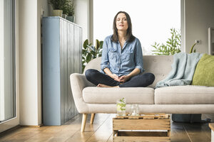 Woman sitting on the couch at home with closed eyes - UUF17239