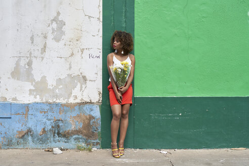 Afro woman on a green and blue wall holding flowers. Baixa, Moçambique, Maputo. - VEGF00002