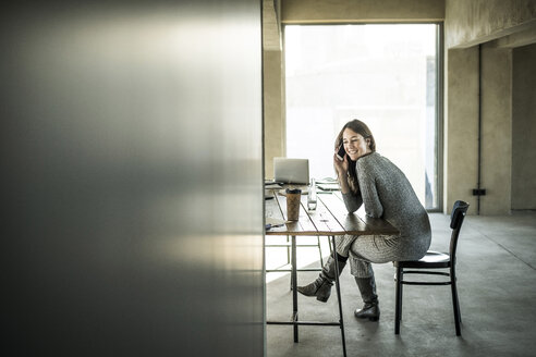 Woman sitting in office, using smartphone - MJRF00176