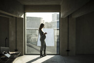 Pregnant businesswoman standing at office window, using smartphone - MJRF00182
