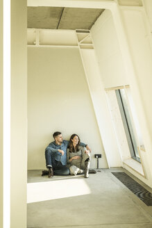 happy couple, expecting baby, sittig on floor of their new apartment - MJRF00194