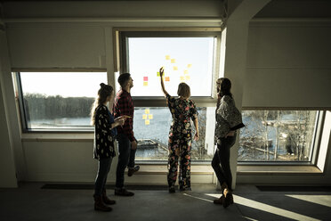 Creative professinal standing in office, brainstorming, putting sticky notes on a window - MJRF00203