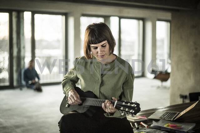 Businesswoman playing the ukulele in office - MJRF00206