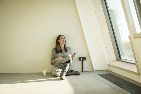 Pregnant woman drinking tea, sitting on floor of her new home - MJRF00212