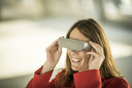 Smiling businesswoman looking through VR goggles - MJRF00221
