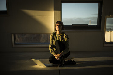 Businesswoman with laptop,  sitting on office floor at sunset, with eyes closed - MJRF00230