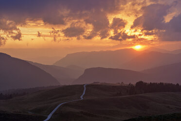 Italy, Dolomites, Passo Rolle, dirt road in the mountains at sunset - RUEF02163