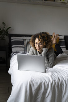 Woman lying on bed, using laptop, surfing the net - FMOF00550