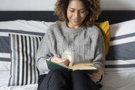 Woman sitting on bed, reading book - FMOF00556
