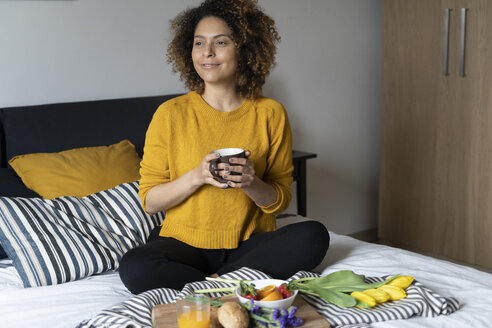 Woman sitting on bed, having a healthy breakfast - FMOF00565