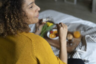 Woman sitting on bed, having a healthy breakfast - FMOF00568