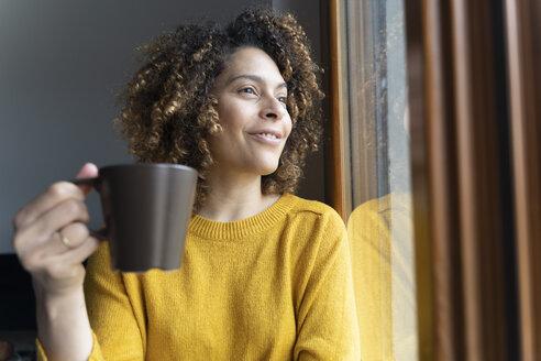 Woman sitting at window, taking a break, drinking coffee - FMOF00580