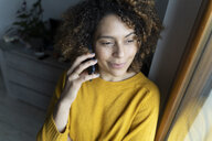 Woman talking on the phone, looking out of window - FMOF00583
