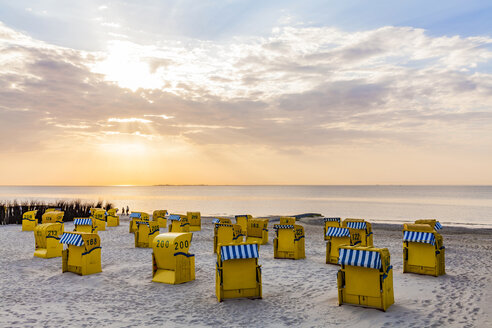 Germany, Lower Saxony, Cuxhaven, Duhnen, beach with hooded beach chairs at sunrise - WDF05242