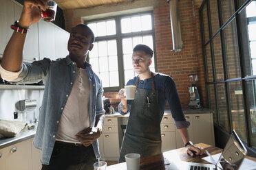 Entrepreneurial coffee roasters examining coffee in kitchen - HEROF35828