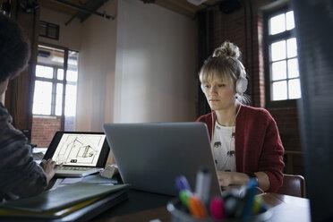 Designer with headphones using laptop in office - HEROF35846