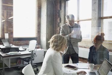 Business people discussing paperwork in meeting - HEROF35948