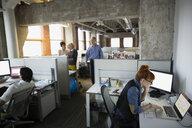 Business people working at desks open plan office - HEROF35954