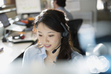 Businesswoman wearing headset at desk in office - HEROF35966