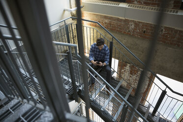 Businessman texting with cell phone in stairwell - HEROF35972