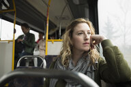 Pensive woman riding bus looking out window - HEROF35981