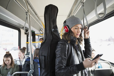 Musician guitar case texting cell phone on bus - HEROF35987