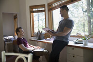 Homosexual couple with digital tablet and laptop in home office - HEROF36041