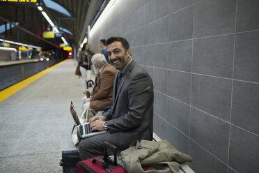 Portrait smiling businessman laptop bench subway station platform - HEROF36065