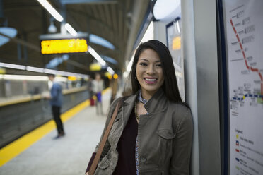 Portrait smiling young woman on subway station platform - HEROF36068