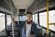 Portrait confident young man headphones digital tablet bus - HEROF36080