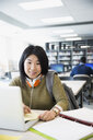 Portrait smiling college student with headphones researching at laptop in library - HEROF36137