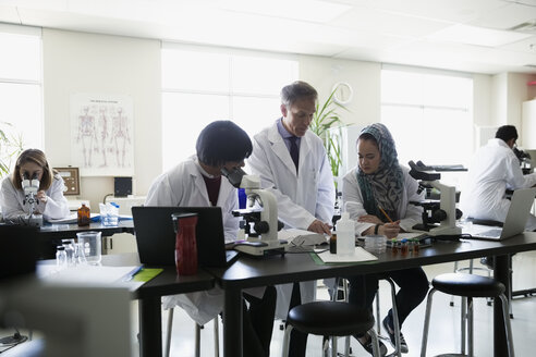 Professor helping students conducting scientific experiment in laboratory - HEROF36152
