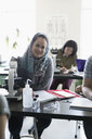 Portrait smiling college student in hijab at microscope in science laboratory - HEROF36155