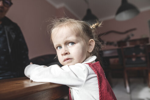 Krefeld, NRW, Deutschland. Ein kleines Mädchen spielt mit dem Tablett auf dem Tisch, Oma sitz im Hintergrund - KMKF00818