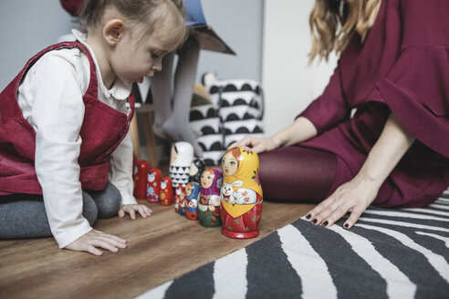 Mother playing with daughter in children's room at home - KMKF00845