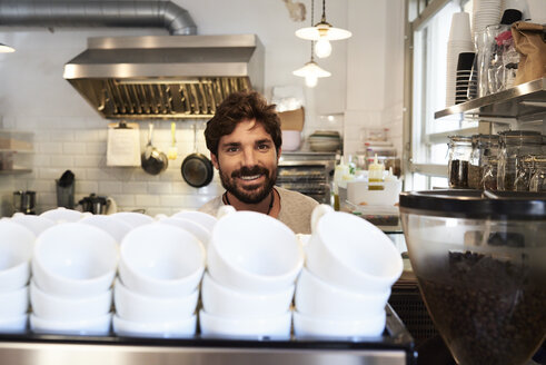 Portrait of smiling barista in a coffee shop - IGGF01151