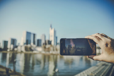 Germany, Frankfurt, hand taking photo of financial district with cell phone - FMKF05542